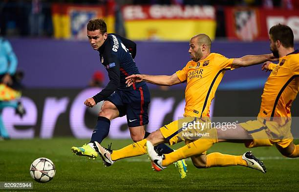 Antoine Griezmann of Atletico Madrid shoots as he is challenged by Javier Mascherano of Barcelona during the UEFA Champions League quarter final...