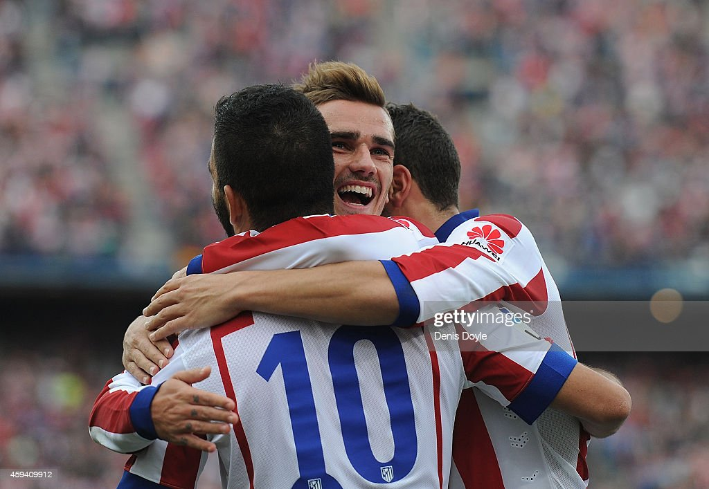 Antoine Griezmann of Club Atletico de Madrid celebrates with Arda Turan after scoring his team's 2nd goal during the La Liga match between Club Atletico de Madrid and Malaga CF at Vicente Calderon Stadium on November 22, 2014 in Madrid, Spain.