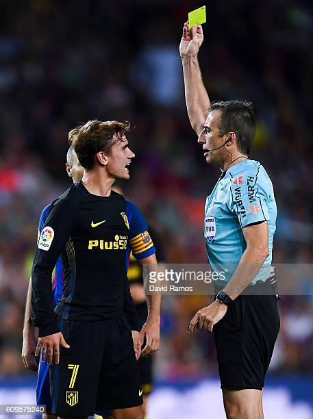 Antoine Griezmann of Club Atletico de Madrid is shown a yellow card by the referee David Fernandez Borbalan after a challlenge on Ardan Turan of FC...