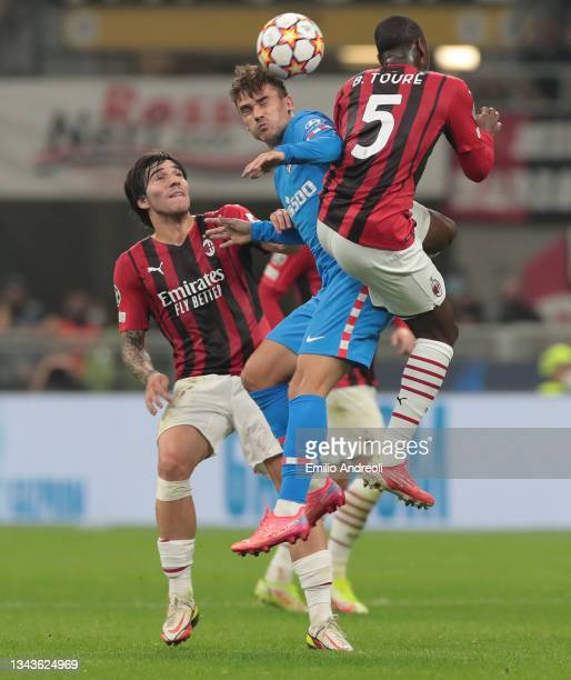 Antoine Griezmann of Club Atletico de Madrid jumps for the ball against Fode Ballo-Toure and Sandro Tonali of AC Milan during the UEFA Champions...