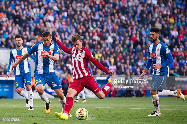 Antoine Griezmann of Club Atletico de Madrid shoots towards goal between Oscar Duarte and Alvaro Gonzalez of Real CD Espanyol and scores his team's...
