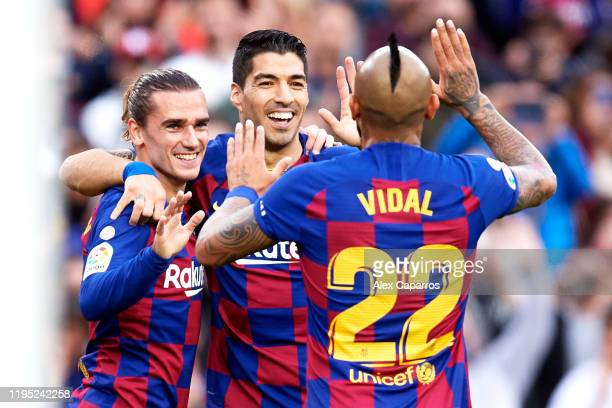 Antoine Griezmann of FC Barcelona celebrates with teammates Luis Suarez and Arturo Vidal after scoring the opening goal during the La Liga match...