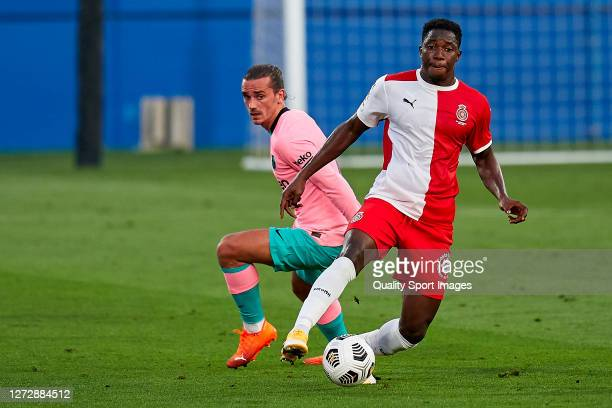 Antoine Griezmann of FC Barcelona competes for the ball with Ibrahima Kebe of Girona FC during the preseason friendly match between FC Barcelona and...