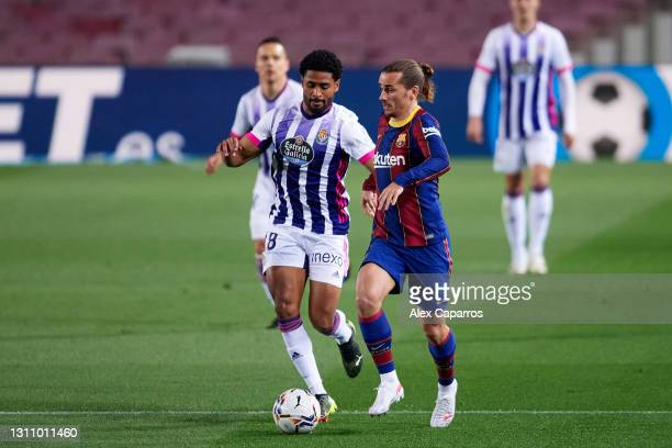 Antoine Griezmann of FC Barcelona competes for the ball with Saidy Janko of Real Valladolid CF during the La Liga Santander match between FC...