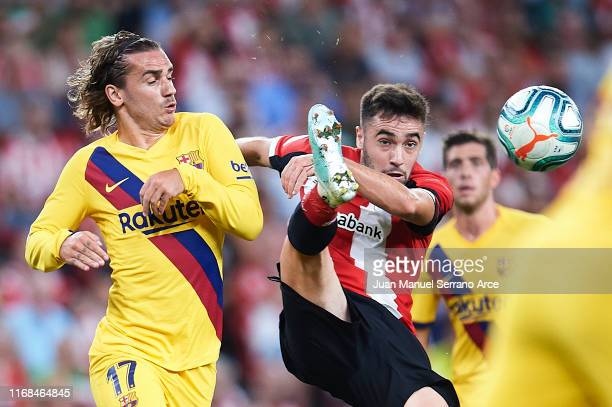 Antoine Griezmann of FC Barcelona competes for the ball with Unai Lopez of Athletic Club during the Liga match between Athletic Club and FC Barcelona...
