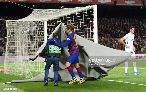 Antoine Griezmann of FC Barcelona helps take a banner off the pitch during the La Liga match between FC Barcelona and Granada CF at Camp Nou on...