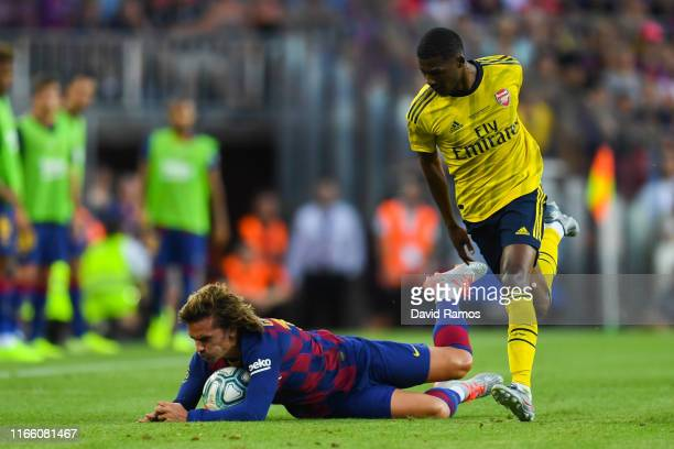 Antoine Griezmann of FC Barcelona is brought down by Ainsley MaitlandNiles of Arsenal during the Joan Gamper trophy friendly match between FC...