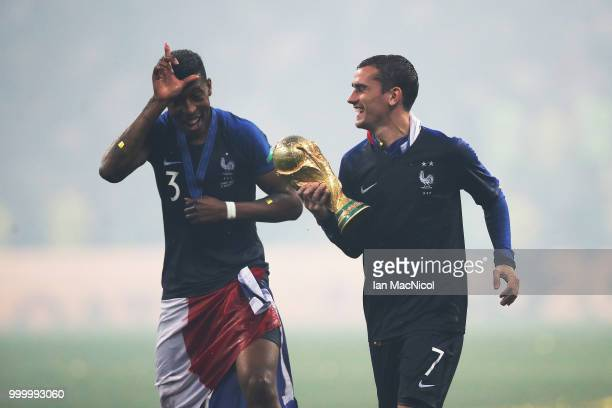 Antoine Griezmann of France and Presnel Kimpembe of France are seen with the trophy during the 2018 FIFA World Cup Russia Final between France and...