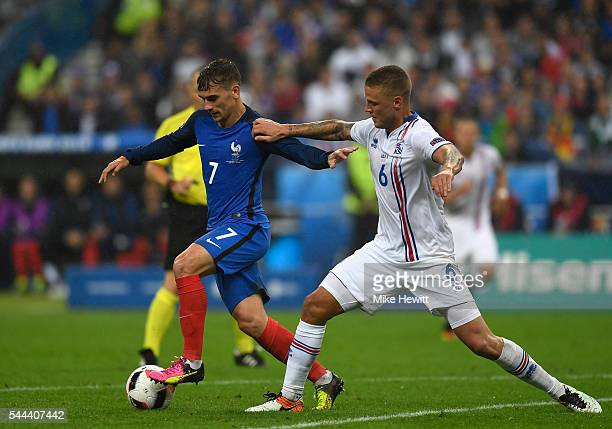 Antoine Griezmann of France and Ragnar Sigurdsson of Iceland compete for the ball during the UEFA EURO 2016 quarter final match between France and...