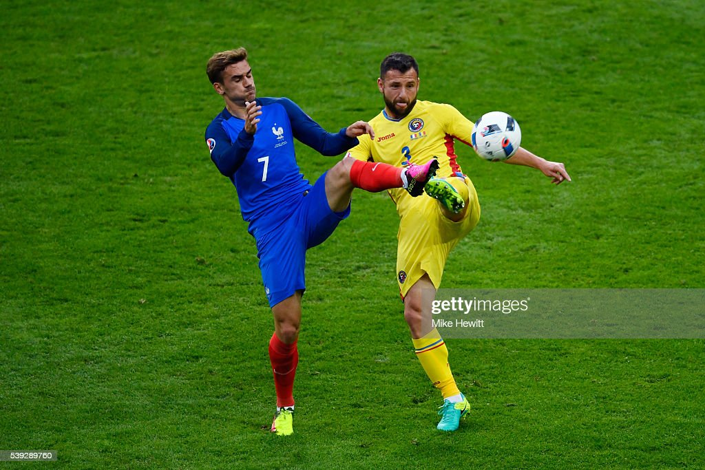 Antoine Griezmann of France and Razvan Rat of Romania compete for the ball during the UEFA Euro 2016 Group A match between France and Romania at Stade de France on June 10, 2016 in Paris, France.