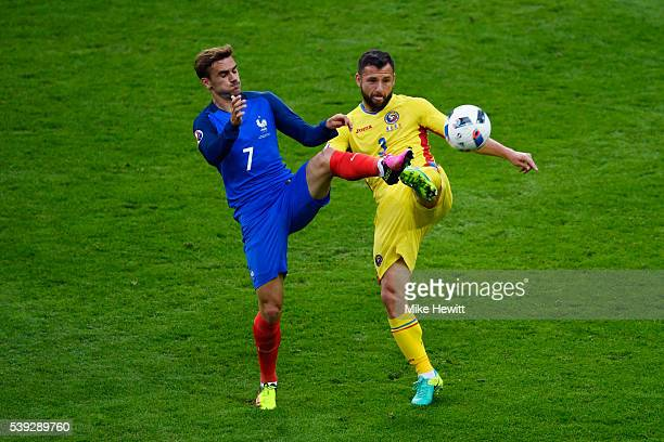 Antoine Griezmann of France and Razvan Rat of Romania compete for the ball during the UEFA Euro 2016 Group A match between France and Romania at...