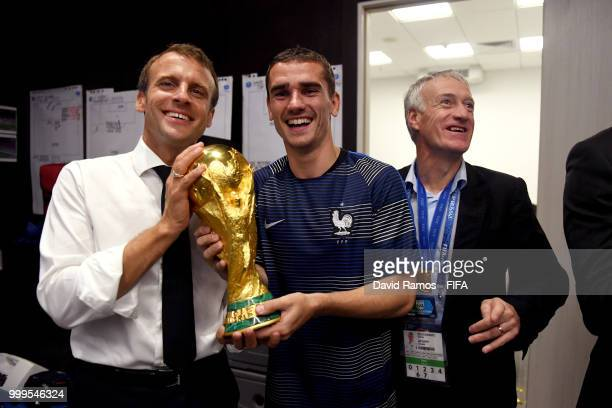 Antoine Griezmann of France and The President of France Emmanuel Macron celebrate with the World Cup Trophy in the dressing room following France's...