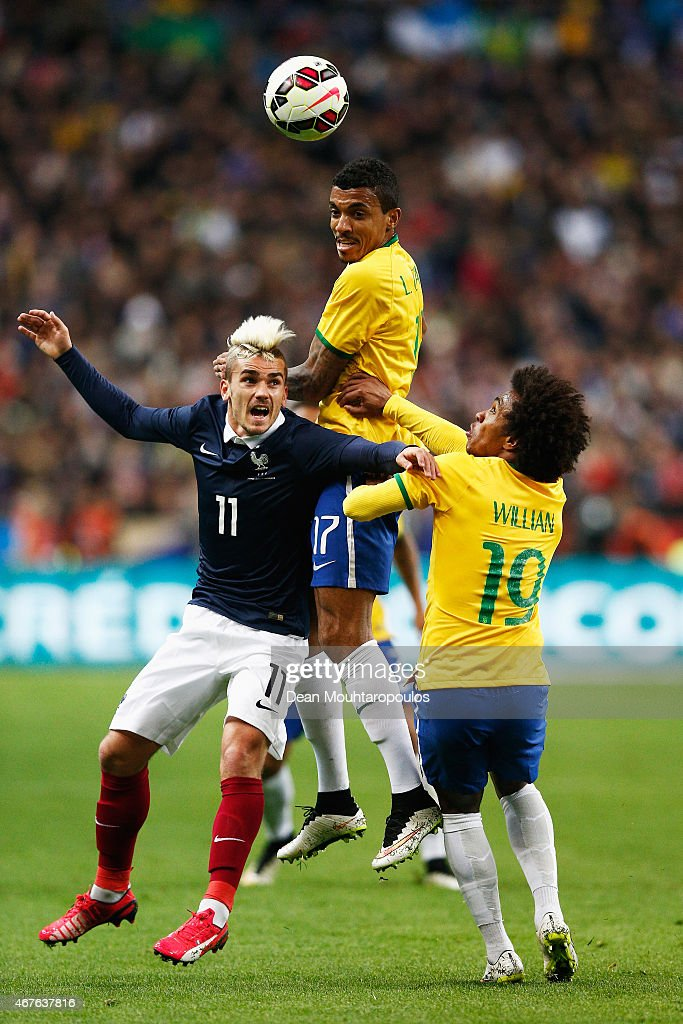 Antoine Griezmann of France battles for the header with Luiz Gustavo and Willian of Brazil during the International Friendly match between France and Brazil at the Stade de France on March 26, 2015 in Paris, France.