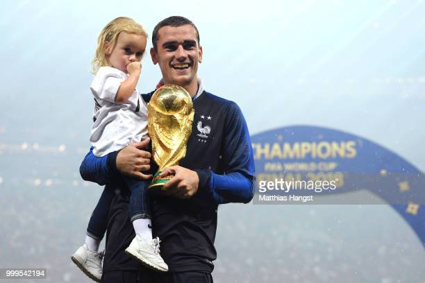 Antoine Griezmann of France celebrates victory with daughter Mia and the World Cup trophy following the 2018 FIFA World Cup Final between France and...