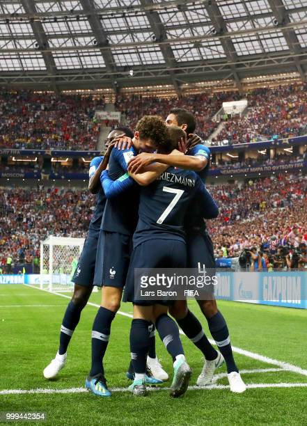 Antoine Griezmann of France celebrates with team mateas following their team's first goal an own goal by Mario Mandzukic of Croatia during the 2018...