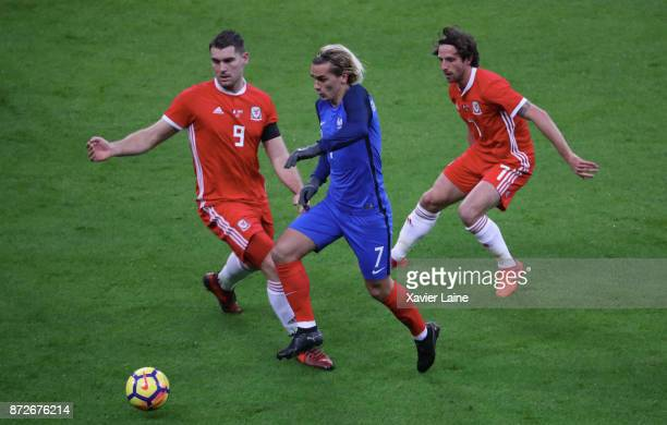 Antoine Griezmann of France in action with Sam Vokes and Joe Allen of Wales during the friendly match between France and Wales at Stade de France on...
