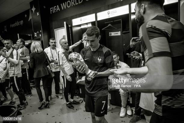Antoine Griezmann of France looks at the World Cup Trophy in the France's dressing room following his side victory in the 2018 FIFA World Cup Russia...