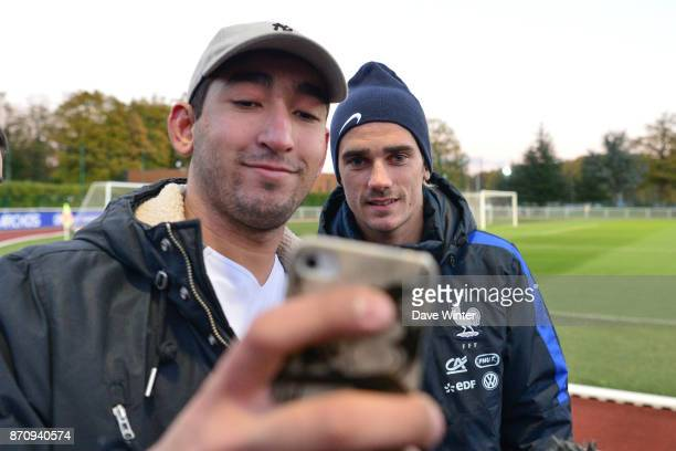 Antoine Griezmann of France poses for a selfie with a fan during the training session at the Centre National de Football in Clairefontaine en...