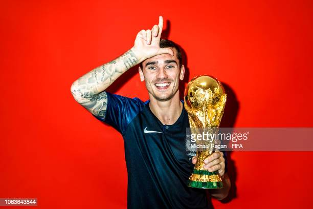 Antoine Griezmann of France poses with the Champions World Cup trophy after the 2018 FIFA World Cup Russia Final between France and Croatia at...