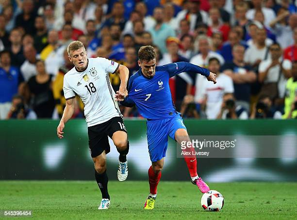 Antoine Griezmann of France runs with the ball under pressure from Toni Kroos of Germany during the UEFA EURO semi final match between Germany and...