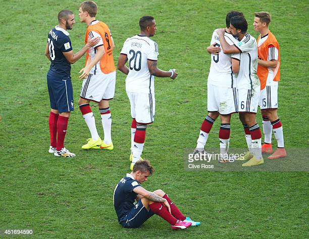 Antoine Griezmann of France sits on the field as Germany celebrates defeating France 10 during the 2014 FIFA World Cup Brazil Quarter Final match...