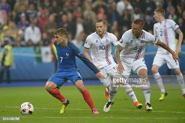 Antoine Griezmann of France with Ragnar Sigurdsson and Gylfi Sigurdsson of Iceland during the UEFA EURO 2016 quarter final match between France and...