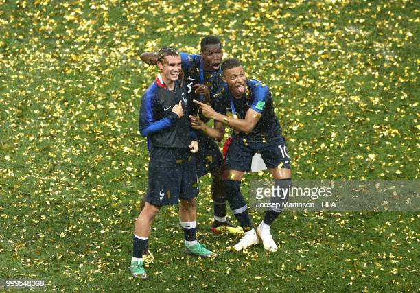 Antoine Griezmann Paul Pogba and Kylian Mbappe of France celebrate victory folowing the 2018 FIFA World Cup Final between France and Croatia at...