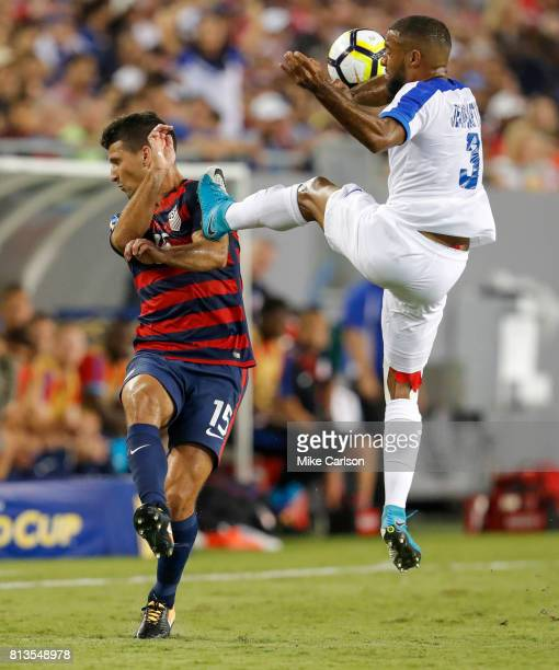 Antoine JeanBaptiste of Martinique kicks high against Eric Lichaj of the United States during the first half of the CONCACAF Group B match at Raymond...