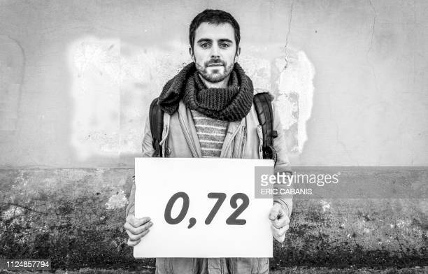 Antoine poses with a placard indicating the level of Glyphosate in their urine before filing a complaint for endangering the lives of others at the...