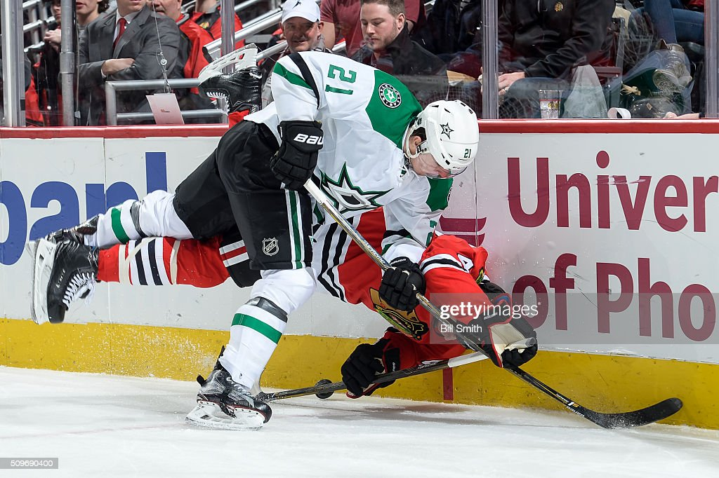 Antoine Roussel #21 of the Dallas Stars hits Rob Scuderi #47 of the Chicago Blackhawks in the second period of the NHL game at the United Center on February 11, 2016 in Chicago, Illinois.