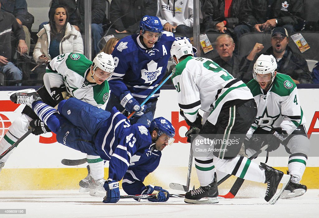 Antoine Roussel #21 of the Dallas Stars upends Nazem Kadri #43 of the Toronto Maple Leafs during an NHL game at the Air Canada Centre on December 2, 2014 in Toronto, Ontario, Canada. The Leafs defeated the Stars 5-3.