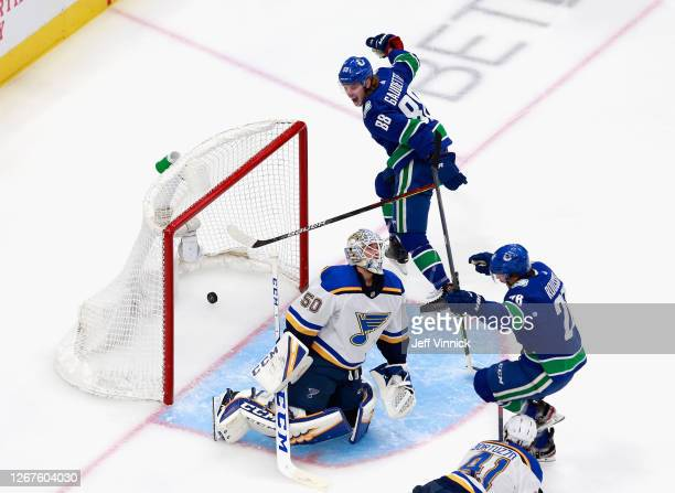 Antoine Roussel of the Vancouver Canucks scores at 209 of the second period against Jordan Binnington of the St Louis Blues and is joined by Adam...