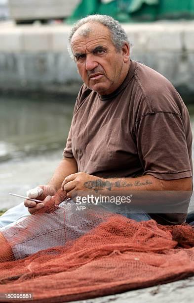 'SUR LA COTE D'AZUR LES PECHEURS ARTISANAUX VEULENT RESTER MAITRES A BORD' Antoine Saïssy un pêcheur du CrosdeCagnes recoud un filet sur un quai du...