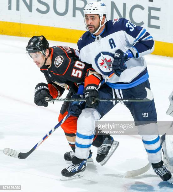 Antoine Vermette of the Anaheim Ducks and Dustin Byfuglien of the Winnipeg Jets battle for position during the third period of the game at Honda...