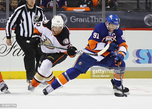 Antoine Vermette of the Anaheim Ducks holds up John Tavares of the New York Islanders during the first period at the Barclays Center on October 16...