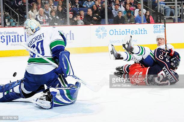 Antoine Vermette of the Columbus Blue Jackets beats goaltender Andrew Raycroft of the Vancouver Canucks as he is knocked over by Christian Ehrhoff of...