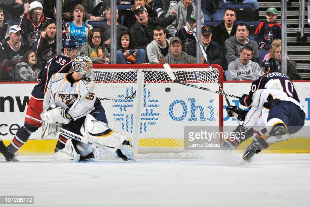 Antoine Vermette of the Columbus Blue Jackets flips the puck into the net past goaltender Pekka Rinne of the Nashville Predators after picking up the...