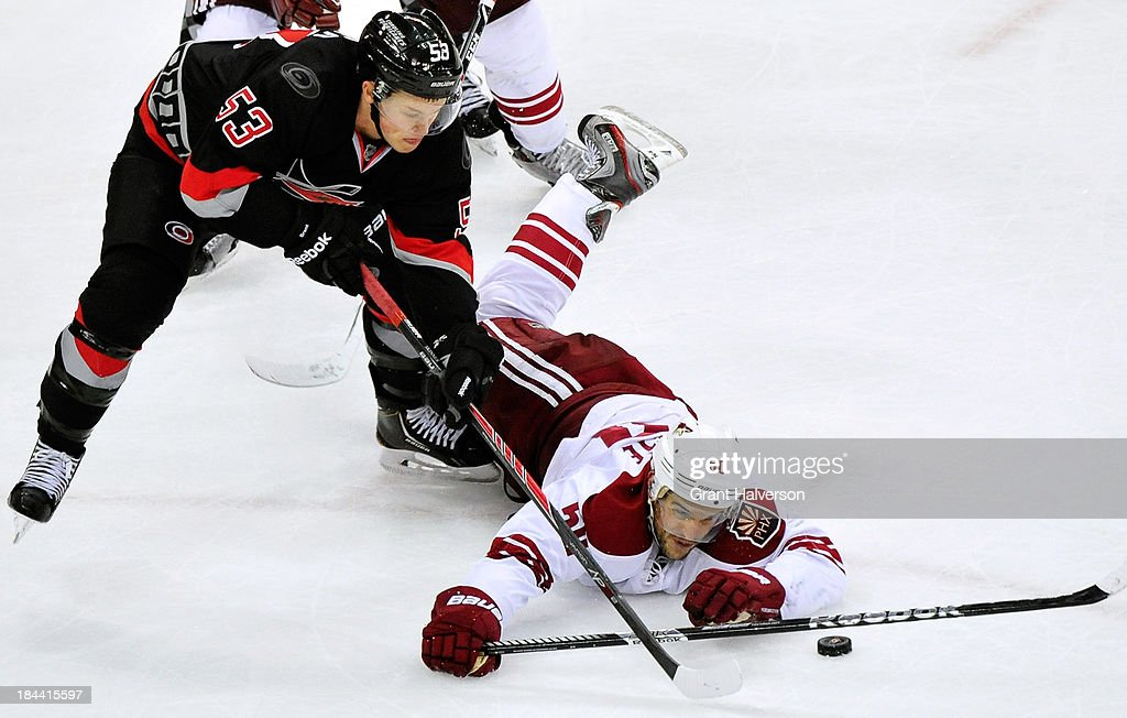Antoine Vermette #50 of the Phoenix Coyotes dives to knock the puck away from Jeff Skinner #53 of the Carolina Hurricanes during play at PNC Arena on October 13, 2013 in Raleigh, North Carolina. The Coyotes won 5-3.