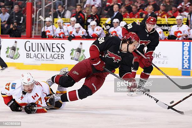 Antoine Vermette of the Phoenix Coyotes falls to the ice as he attempts to play the puck past Derek Smith of the Calgary Flames during the first...
