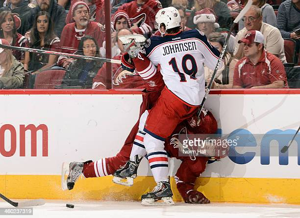 Antoine Vermette of the Phoenix Coyotes is checked into the boards by Ryan Johansen of the Columbus Blue Jackets during the second period at...