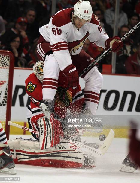 Antoine Vermette of the Phoenix Coyotes lands on Corey Crawford of the Chicago Blackhawks as Crawford makes a save in Game Three of the Western...