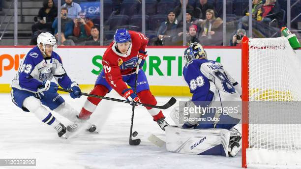 Antoine Waked of the Laval Rocket taking a shot on Eddie Pasquale of the Syracuse Crunch with Alexander Volkov of the Syracuse Crunch trying to help...