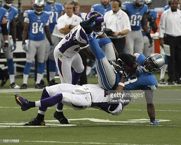 Antoine Winfield and Josh Robinson of the Minnesota Vikings team up and tackle Nate Burleson of the Detroit Lions at Ford Field on September 30 2012...