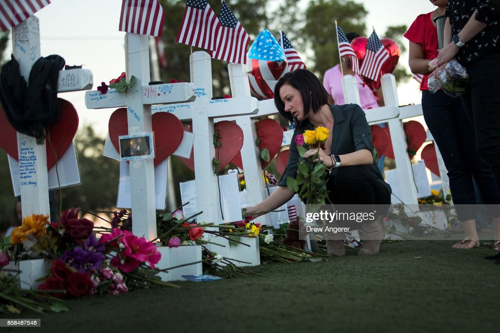Antoinette Cannon, who worked as a trauma nurse and treated victims last Sunday night, leaves a rose at each of the 58 white crosses at a makeshift memorial on the south end of the Las Vegas Strip, October 6, 2017 in Las Vegas, Nevada. On October 1, Stephen Paddock opened fire on the crowd at the Route 91 Harvest country music festival, killing 58 people and injuring more than 450. The massacre is one of the deadliest mass shooting events in U.S. history.