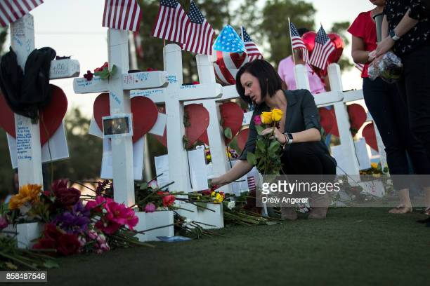 Antoinette Cannon who worked as a trauma nurse and treated victims last Sunday night leaves a rose at each of the 58 white crosses at a makeshift...