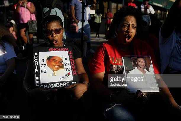 Antoinette Marshabanks left holds a photos of her son Archie Lee Chambers Jr and Sharon Miles holds a picture of her son Korey Parker during a sitin...