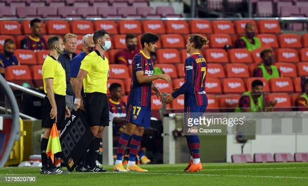 Antoinne Griezmann of FC Barcelona greets Francisco Trincao of FC Barcelona as Francisco Trincao is substituted on and Antoine Griezmann is...