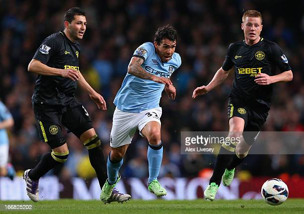 Antolin Alcaraz and James McCarthy of Wigan Athletic compete with Carlos Tevez of Manchester City during the Barclays Premier League match between...