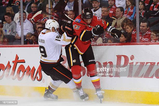 Anton Babchuk of the Calgary Flames gets checked by Matthew Lombardi of the Anaheim Ducks during an NHL game at Scotiabank Saddledome on April 19...