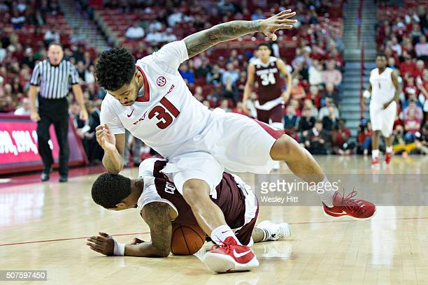 Anton Beard of the Arkansas Razorbacks goes for a loose ball and falls over Anthony Collins of the Texas AM Aggies at Bud Walton Arena on January 27...